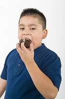Pre-teen (10-12) boy eating cookie