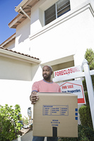 Sad mid adult man moving out of house