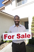 Man holding 'for sale' notice