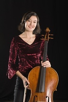 Female cellist stands with cello, portrait