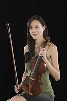 Young Asian woman sits holding a violin