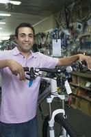Bike shop assistant stands holding new bike