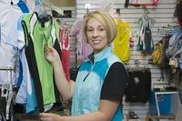 Female cyclist in bike shop choosing cycling top