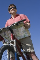 Mature man stands looking at map with mountain bike