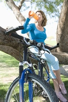 Mature woman drinking water on a tree with her bike