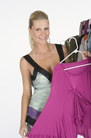 Woman chooses a pink blouse from a selection of items on a clothes rail