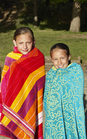 Two Girls (7-9) wrapped in towels, outdoors.