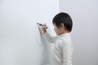 ホワイトボードに絵を描く子供