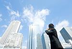 右側のビルを見ながら電話をするビジネスマン