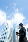 手帳を片手に右側のビルを見ているビジネスマン