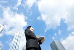 ノートパソ コンを片手に上を向いているビジネスマン