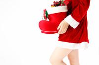 クリスマスプレゼントを運ぶコスプレ女性サンタ