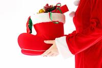 クリスマスプレゼントを持つコスプレ女性サンタ