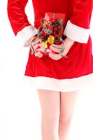 後ろ手にクリスマスプレゼントを持つ女性サンタ