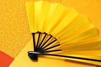 和柄の黄色い風呂敷に置いた金の扇子