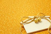 花柄模様の布に置いた金の鈴付き絵馬