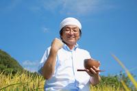 農業 豊作の田んぼでガッツポーズする男性