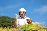 農業 稲刈りと田んぼでガッツポーズする男性