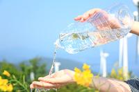 風力発電機の並ぶ自然とペットボトルの水と女性の手