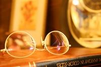 書斎机の本に乗せた金色のメガネ