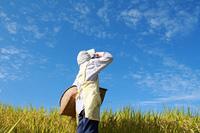 田んぼで休憩日本人女性の農業作業