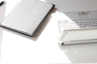 白い机とノートパソ コンと書類と手帳