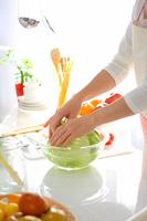 キッチンでサラダ調理する女性 縦