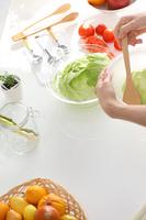 キッチンで家庭料理する女性の手 縦