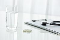 水が入ったコップとカプセル型の薬