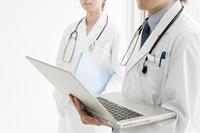 パソコンを持つ医師と女医