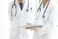 カルテを見て相談しあう医師と女医