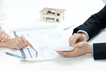家の設計図で説明をするビジネスマン