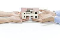 家の模型を持つ2人