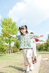 バランスを取りながら丸太の上を歩く少年と少女