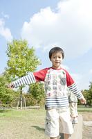 バランスを取りながら丸太の上を歩く少年