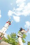 両手を上げながら丸太の上から飛ぶ少年と少女