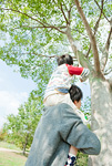虫取り網で虫を捕ろうとする親子