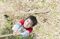 虫取り網で虫を捕ろうとする少年