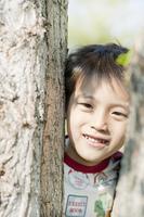 木の間から顔を覗かせる少年