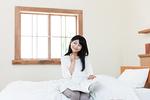 ベッドルームで雑誌を読む若い女性