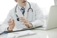 ノートパソ コンを確認する医師