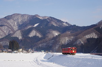 雪晴れの里を行くディーゼルカー