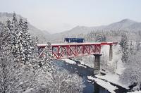 雪景色の阿仁川を渡る