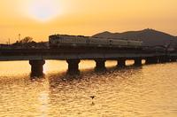 夕焼けの船越水道を渡る列車