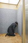 エレベーターの隅で落ち込むビジネスマン