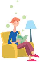 ソファに座って本を読む女性
