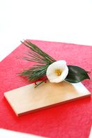 和紙の上の絵馬と白い椿の花