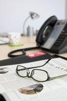 オフィス 机の上の新聞と眼鏡