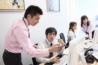 パソコンを見つめ話し合いをするビジネスマンとビジネスウーマン