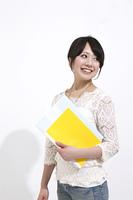 黄色いノートを持つ笑顔の女性